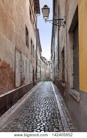 Old narrow street with a stone blocks and lanterns in perspective.