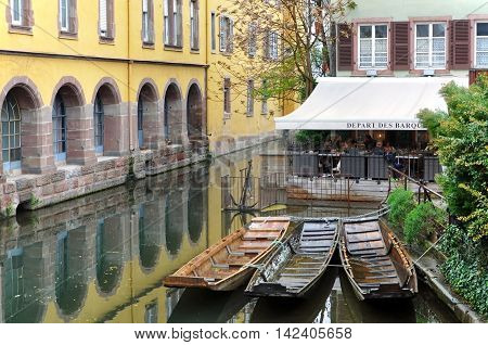 COLMAR,  FRANCE - APRIL 23, 16: The old city water canal with old houses on one side and a street cafe on the other side. Three wooden boat in the foreground. Colmar, Alsace, France.