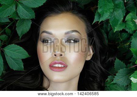 Girl Lying In The Green Foliage