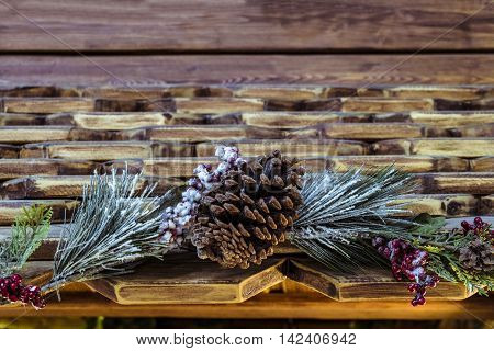 Christmas fir branch with pinecone on the decorative wooden shards