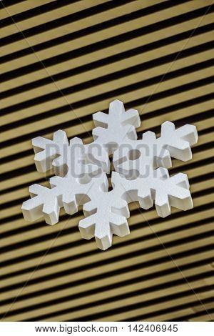 Volumetric Christmas decorative snowflake on striped background