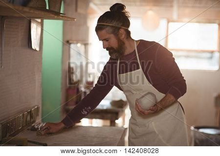 Male potter holding clay and cleaning table in pottery workshop