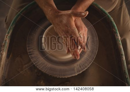 Close-up of male potter making pot in pottery workshop