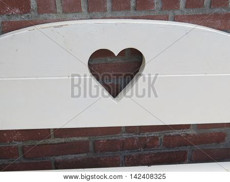 White bench Backrest with heart cutout in village of Urk Holland