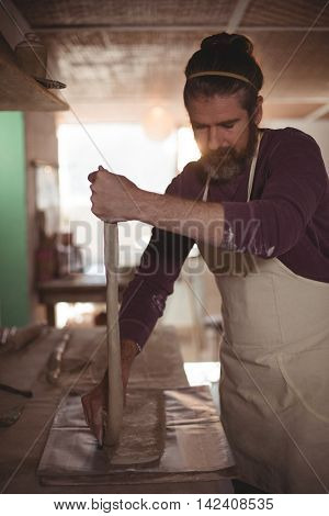 Male potter designing clay with stick in pottery workshop
