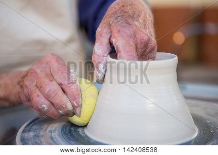 Close-up of potter making pot in pottery workshop