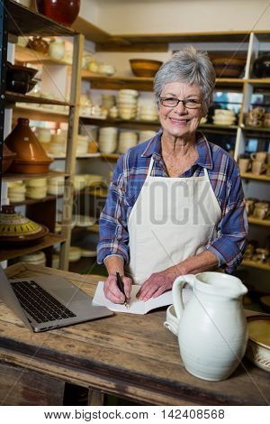 Portrait of female potter making note from laptop in pottery workshop