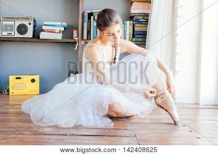 Ballet dancer tying slippers around her ankle woman ballerina pointe.