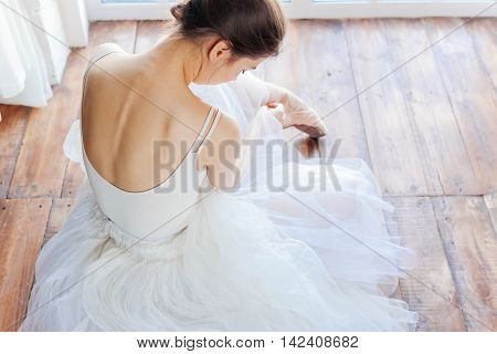 A beautiful ballerina, back view on wood background.