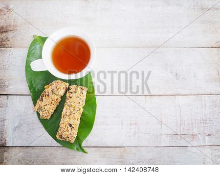 White cup of tea and healthy granola on green leaf over wood background