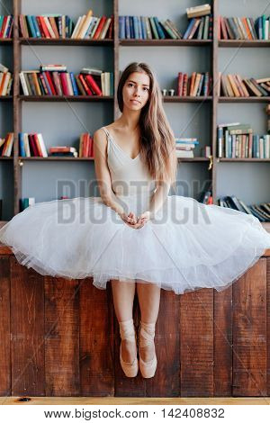 Dancer in a tutu and dress in library.