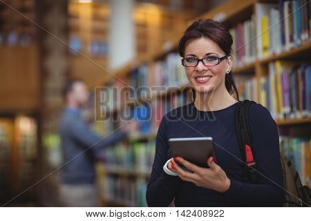 Portrait of mature student holding digital tablet in college library