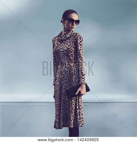 Fashion luxury woman wearing a leopard dress and handbag clutch evening in city