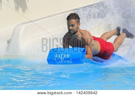 Rhodes Greece-August 1,2016:Young men on the mat racer slide.Mat racer slide is very popular for young people in the Water Park.Water Water Park is located on the island of Rhodes in Greece and one of the most largest in Europe and is a very popular place