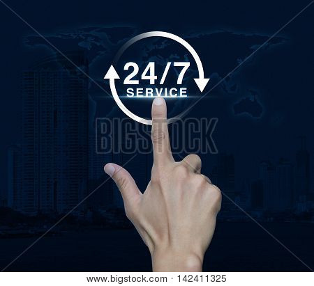 Hand pressing button 24 hours service icon over map and city tower Full time service concept Elements of this image furnished by NASA