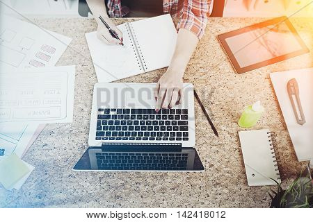 Woman typing and writing in notebook at cork table in office. Concept of multitasking. Toned image