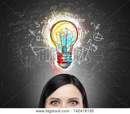 Close up Woman's head against blackboard with colorful light bulb sketch surrounded by formulas. Concept of new original idea