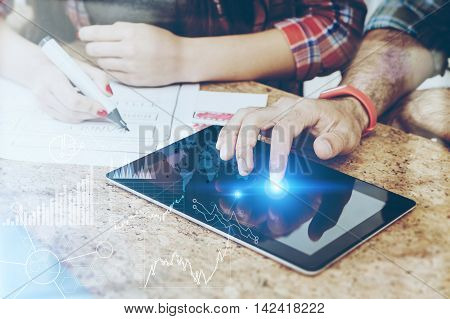 Man working with tablet. His colleague drawing sceme. Concept of web design. Toned image. Double exposure. Elements of this image furnished by NASA