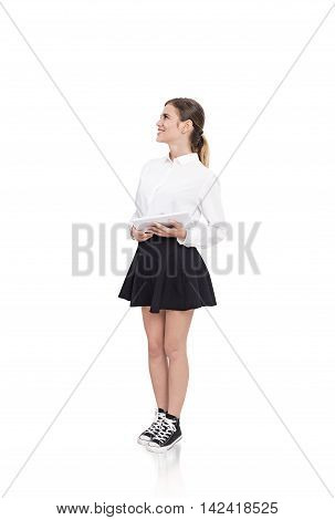 Smiling young lady in white shirt short black skirt and converse holding tablet and looking sideways