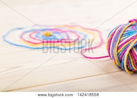Large bundle of wool lie on wooden table with its thread curled in spiral. Concept of hobby and free time. Close up. Top view.