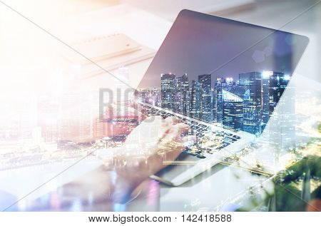 Man's hands typing . City on foreground. Concept of clerk work in modern bank business. Toned image. Double exposure