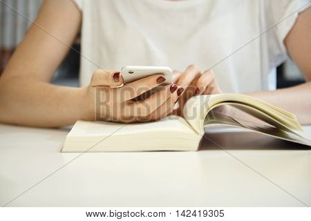 Cropped Shot Of Female With Neat Manicure Wearing White Blouse With Her Hands On An Open Book, Brows