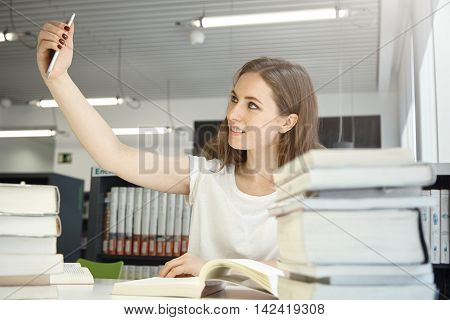 Human And Technology. People And Education. Indoor Portrait Of Caucasian Teenage Girl At Library Try