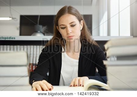 Beautiful Teenage Girl With Long Brunette Hair Wearing Uniform Studying Textbook Or Manual, Listenin