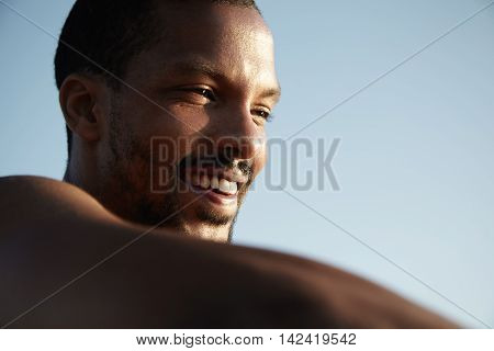 Close Up View Of Handsome Happy Dark-skinned Man With Healthy Skin And Cheerful Smile Looking Into D