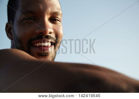 Cropped Portrait Of Joyful Young African Man With Small Beard Sitting On Pavement Enjoying Sunny Wea