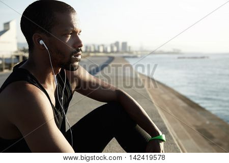 Beautiful Sideways Shot Of Young African American Man Looking In Front Of Him And Contemplating Wate