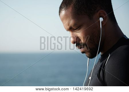 Sideways Shot Of Sad African American Man Looking Down And Listening To Melancholic Music In Headpho