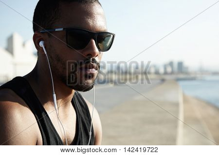 Attractive Dark-skinned Runner Wearing Shades And Black Sportswear Relaxing After Hard Intensive Tra