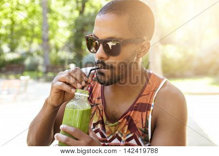 Healthy Organic Food. Half Profile Portrait Of Dark Skinned Guy Drinking Tasty Fresh Green Smoothie