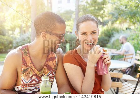 Beautiful Interracial Couple Sipping Smoothies During Date. Caucasian Girl And Handsome African Man