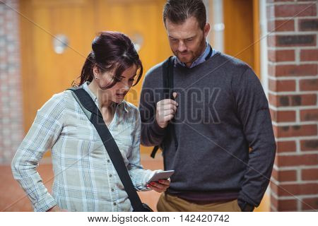 Mature students discussing over mobile phone in the university