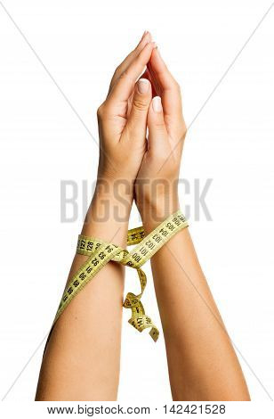 Beautiful woman hand bound a measure tape on a white isolated background