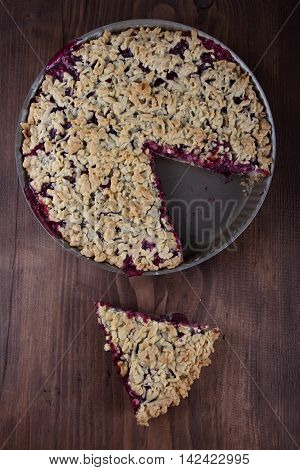 Pie pastry stuffed with black currant in a baking pan. A piece of cake beside on the table.