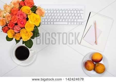 Feminine startup concept, office desk workspace with roses, computer keyboard and notepad on white background. Hipster style mockup.