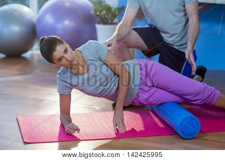 Physiotherapist assisting woman while exercising on exercise mat in clinic