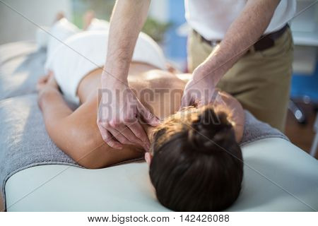 Physiotherapist giving physical therapy to the neck of a female patient in the clinic