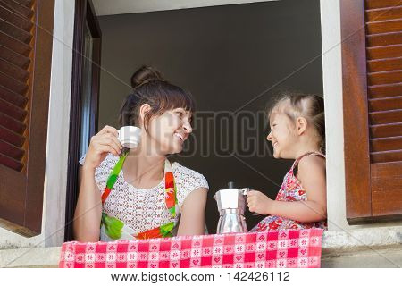 Laughing and looking at each other mother with two years old daughter are holding traditional Italian coffee set of white cup and metal moka pot