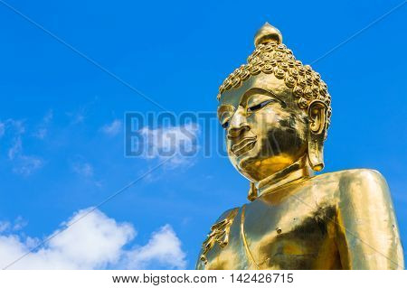 Thai golden Buddha with blue sky background