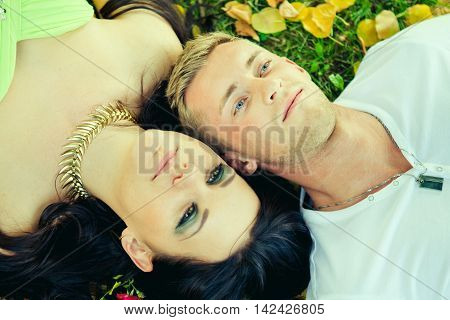 Attractive the guy with the girl lie on a grass closeup