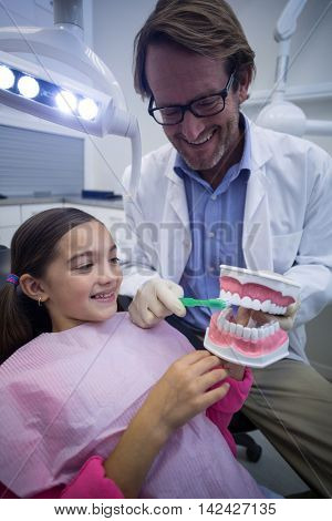 Dentist showing young patient how to brush teeth in dental clinic