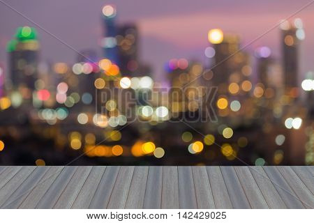 Opening wooden floor, blurred lights city office building night view, abstract background