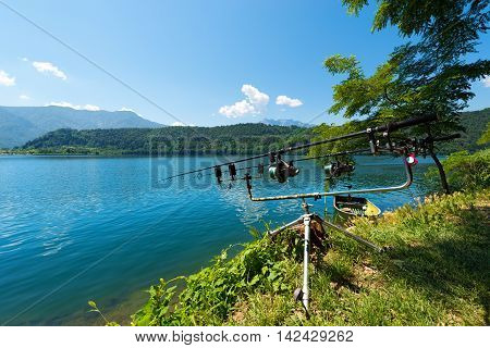 Two fishing rods with reels on a support system (rod pod) at Levico Lake (Lago di Levico) in Trentino Alto Adige Italy Europe