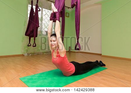 Woman making yoga exercises with hammock on the mat indoor