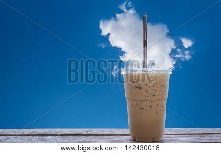 Iced coffee on wooden blue sky with beautiful could background.