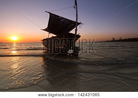 the boat on low tide beach when sunset